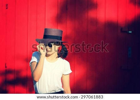 Fashion style portrait of young trendy girl with brown hat. Model posing and standing near red wall.  (Color Process)