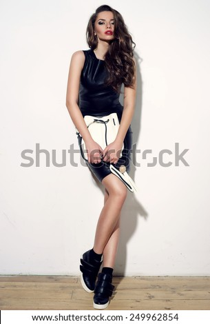 Fashion style studio portrait of young stunning woman in black sexy minidress with white handbag. Beautiful girl with long curly hair and red lips. - stock photo