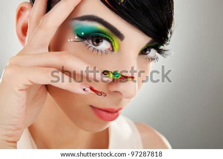 Fashion style. Woman face with so sexy  color makeup and finger nails