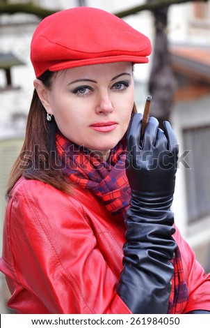 Fashion style woman smoking wearing red hat,black gloves and red leather jacket. - stock photo