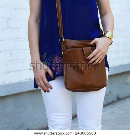 fashion style young trendy girl with leather brown handbag and white jeans walking along the street - stock photo