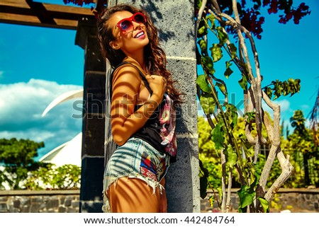 fashion stylish beautiful young smiling brunette woman model in summer hipster bright colorful casual clothes posing in the street - stock photo