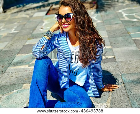 fashion stylish beautiful young smiling brunette woman model in summer hipster casual blue clothes sitting in the street in sunglasses
