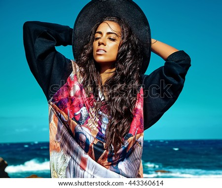 fashion stylish beautiful young smiling brunette woman model in summer hipster casual clothes posing behind blue ocean and sky background in hat - stock photo