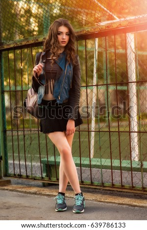 Fashion stylish beautiful young woman model in summer hipster colorful casual clothes posing on street background