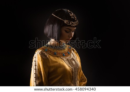 Fashion Stylish Beauty Portrait with Black Short Haircut and Professional Make-Up of Cleopatra Over Black. Beautiful Girl's Face Close-up. - stock photo