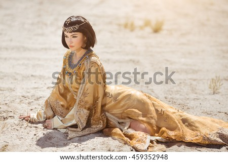 Fashion stylish beauty woman with black short haircut and professional make-up of Cleopatra. Girl sitting in golden dress outdoors in desert. Hot sunny weather. - stock photo