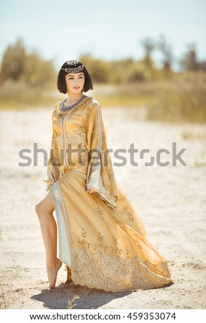 Fashion stylish beauty woman with black short haircut and professional make-up of Cleopatra. Girl standing in full lenght in golden dress outdoors in desert - stock photo