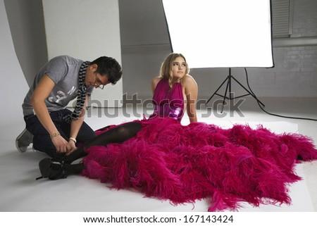 Fashion stylists adjusts model's footwear in studio - stock photo