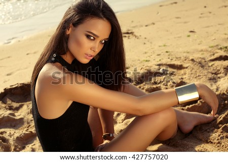 fashion summer outdoor photo of gorgeous sexy girl with dark hair posing on beach - stock photo