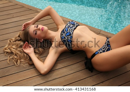 fashion summer outdoor photo of gorgeous woman with blond curly hair in luxurious swimsuit posing beside swimming pool