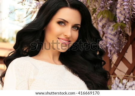 fashion summer outdoor photo of gorgeous woman with long dark hair in elegant dress, posing in blossom garden - stock photo