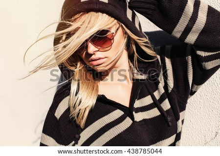 Fashion summer outdoor portrait of young blonde girl posing on the street on light warm wall background in sunglasses  - stock photo