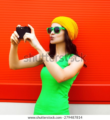 Fashion, summer, technology and people concept - pretty cool girl in sunglasses makes self-portrait on the camera outdoors against colorful red wall - stock photo