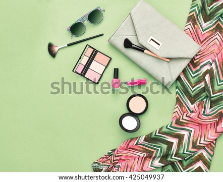 Fashion. Summer woman essentials.Unusual fashion overhead, top view. Summer clothes, cosmetics,makeup accessories fashion set.Urban fashion summer colorful outfit.Stylish handbag clutch, sunglasses.
