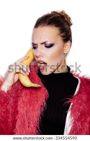 Fashion swag female model wearing black dress and pink fur coat making fun with banana. Woman holding a banana as telephone and having fun over white background not isolated - stock photo