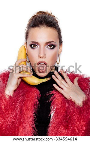 Fashion swag girl wearing black dress and pink fur coat making fun with banana. Woman holding a banana as a telephone over a white background not isolated - stock photo
