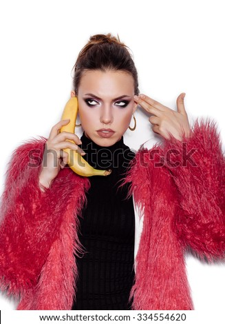 Fashion swag girl wearing black dress and pink fur coat making fun with banana. Woman holding a banana as telephone and having fun over white background not isolated - stock photo