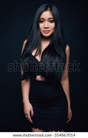 Fashion swag portrait of beautiful elegant asian woman in formal dress on black background - stock photo