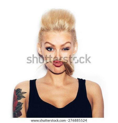 Fashion swag sexy blonde young woman having fun and looking at camera. Girl with bright makeup showing a mustache from the hair. White background, not isolated - stock photo