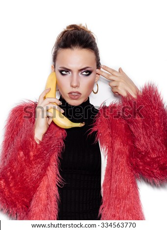 Fashion swag sexy woman wearing black dress and pink fur coat making fun with banana. Woman holding a banana as telephone and having fun over white background not isolated - stock photo