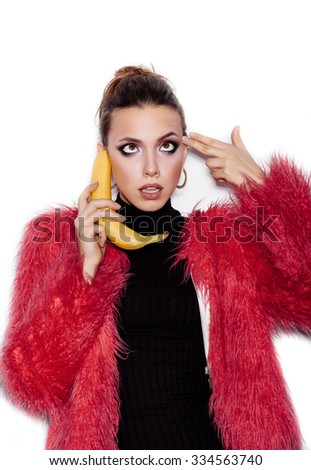 Fashion swag woman wearing black dress and pink fur coat making fun with banana. Woman holding a banana as a telephone and having fun over a white background not isolated - stock photo