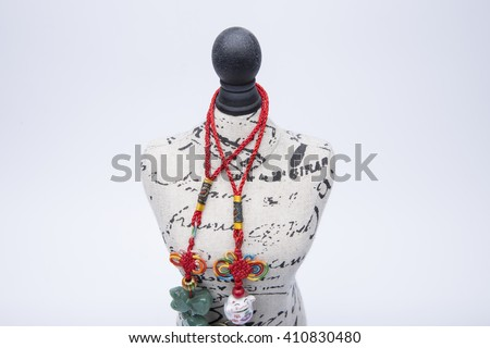 Fashion symbol, mini statuette mannequin with mysterious mystical beads - stock photo