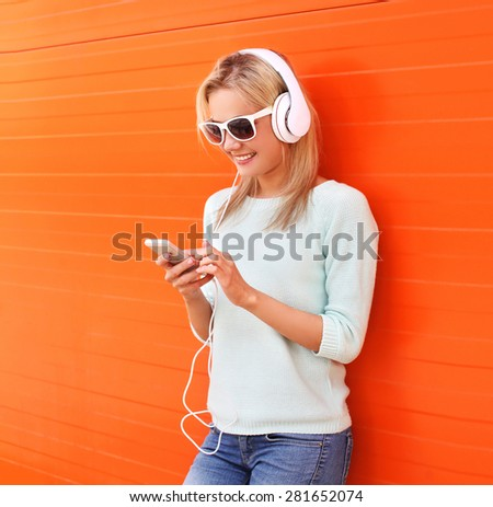 Fashion, technology and people concept - pretty smiling girl listen to music in headphones and using smartphone against the colorful orange wall - stock photo