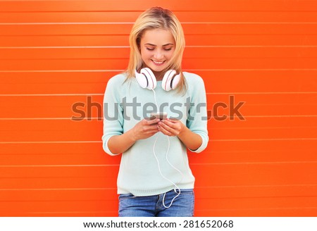 Fashion, technology and people concept - pretty smiling girl using smartphone in headphones against the colorful orange wall - stock photo
