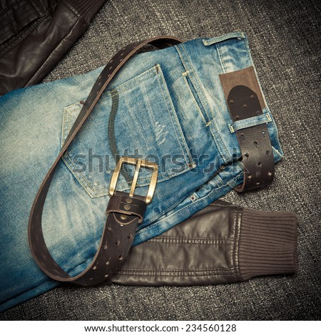 Fashion trend: blue frayed jeans, a leather jacket and leather belt with buckle - stock photo