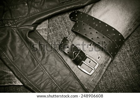 Fashion trend - jeans, leather jacket, leather belt with a buckle. Black and white photo in vintage style - stock photo
