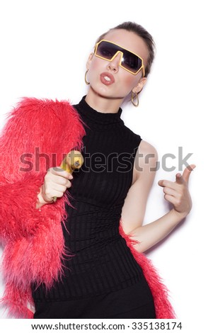 Fashion trendy female model wearing black dress and pink fur coat making fun with banana. Cute girl having fun over white background not isolated - stock photo