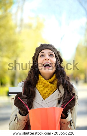Fashion trendy woman opening shopping bag and holding credit card. Blissful brrunette female looking up after purchasing clothes in autumn. - stock photo