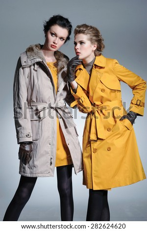 fashion two model in coat clothes posing on light background - stock photo