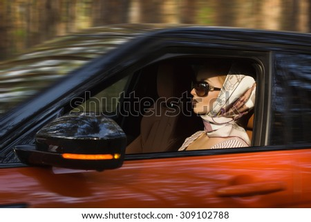 Fashion vintage woman behind steering wheel - stock photo