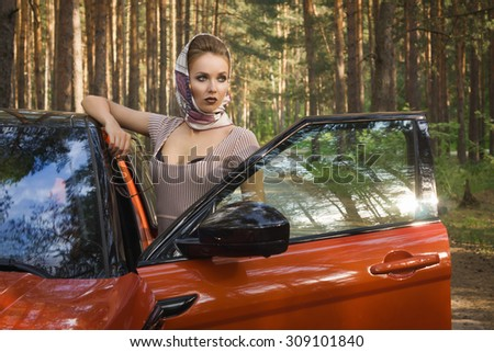 Fashion vintage woman standing near vehicle with opened door