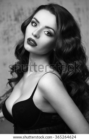 Fashion vogue style beauty portrait of young pretty beautiful brunette woman. Stunning caucasian female model with curly or wavy dark hair and red lips looking at you. Gray wall background - stock photo