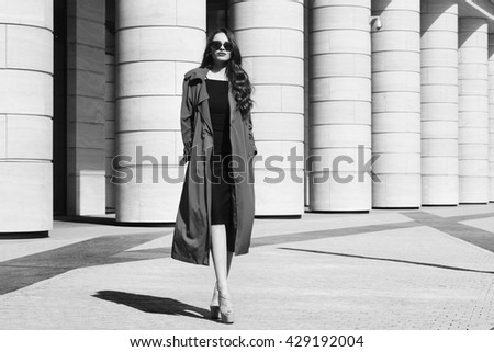 Fashion vogue style dynamic portrait of young beautiful pretty woman posing at city street in black dress, gray coat and sunglasses. Elegant lady with curly hair walking on a sunny windy day