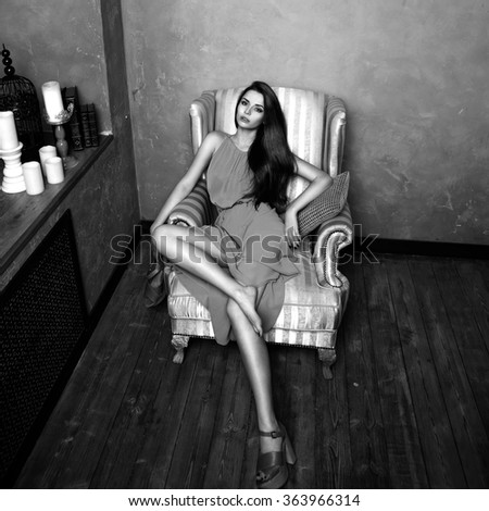 Fashion vogue style portrait of young beautiful female model sitting in a chair in brown wooden interior