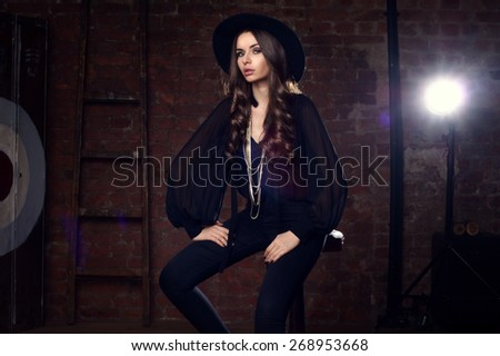 Fashion vogue style portrait of young pretty stylish sitting in loft interior on high barchair in black blouse, trousers, hat and boots - stock photo