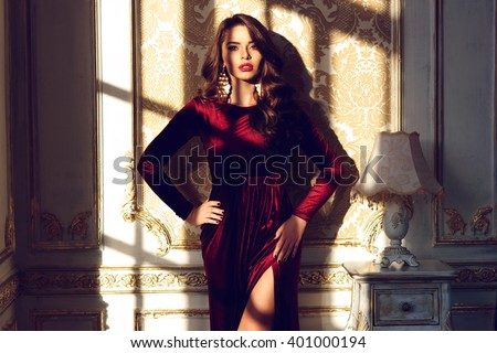 Fashion vogue style portrait of young stunning woman posing in red dress in sunset lightning with shadows in interior. Gorgeous glamorous woman with dark long curly hair