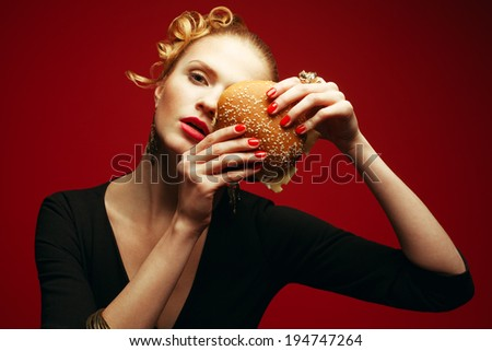 Fashion vs Junk Food Concept. Guilty pleasure. Fashionable model holding burger near face over red background. Perfect hair, skin, make-up & manicure. Golden accessories. Close up. Studio shot - stock photo