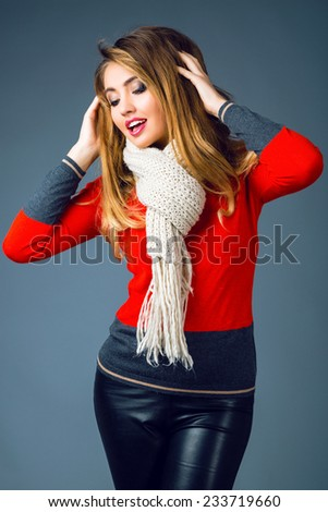 Fashion winter portrait of beautiful blonde woman with sexy smoky make up , wearing bright trendy smart casual sweater, black leather pants and big cozy warm beige scarf.