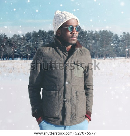 Fashion winter young african man wearing sunglasses and jacket with knitted hat over snowflakes