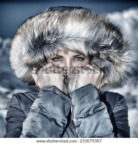 Fashion wintertime look, vintage style photo of gorgeous female wearing warm stylish coat with furry hood, fashionable winter clothes, vogue concept