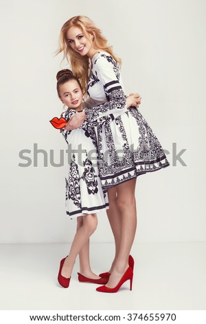 Fashion woman and a pretty little girl wearing the same dresses, red shoes. Photo of mother and daughter - stock photo