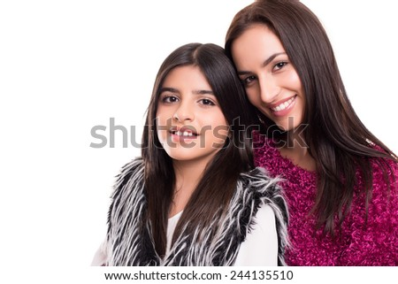 Fashion woman and girl posing over white background