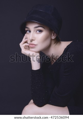 Fashion woman. Black and white portrait of beautiful young elegant lady in black dress and hat. Vintage styling. Beauty, fashion, style. Image toned and noise added.