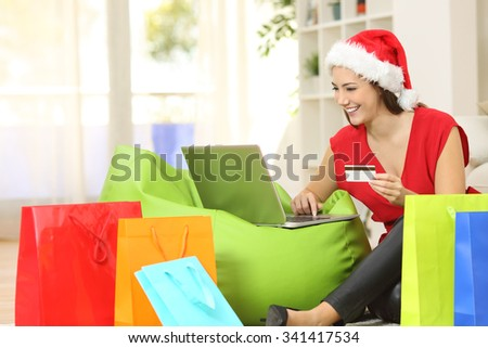 Fashion woman buying online for christmas sitting on the floor with colorful shopping bags at home - stock photo