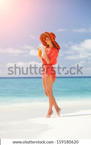 Fashion woman drinking cocktail on the beach - stock photo